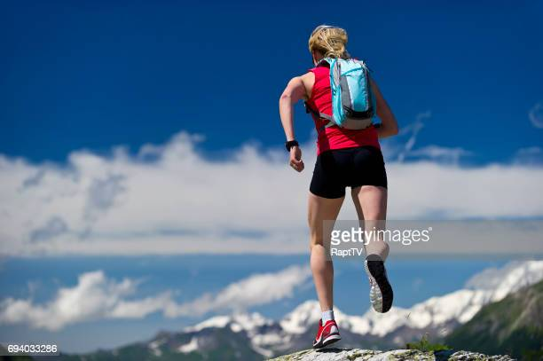 A women running above snowy mountain peaks.