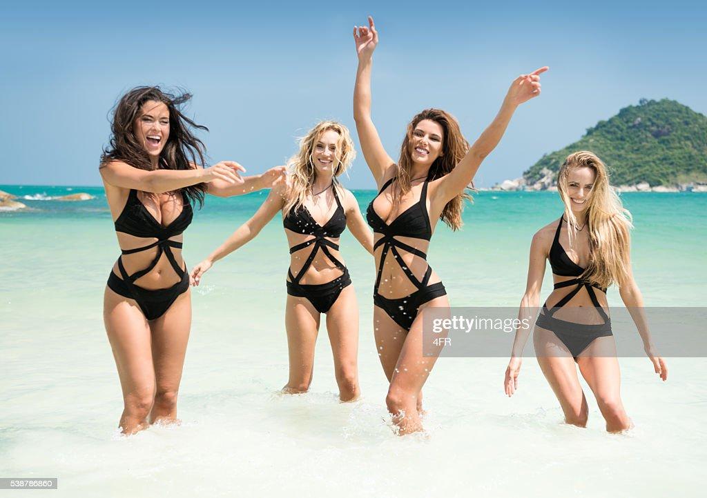 Women running, splashing in the Ocean on Vacation : Stock Photo