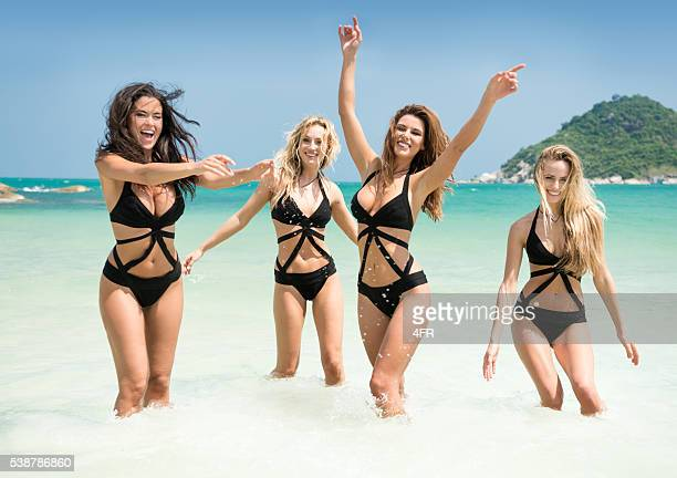 women running, splashing in the ocean on vacation - hot babe stockfoto's en -beelden