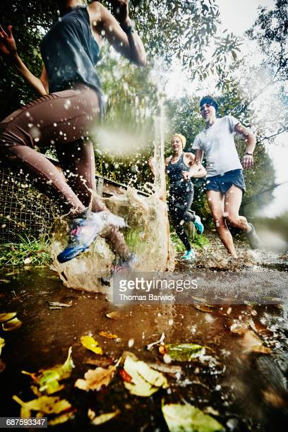 Women running though mud puddle during trail run