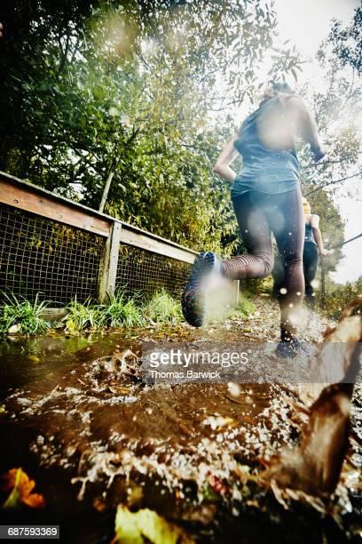 Women running through mud puddle during trail run