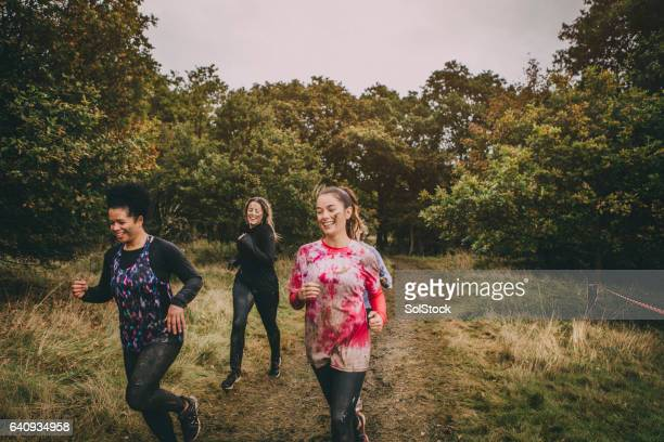 women running through the woods - sports team event stock photos and pictures