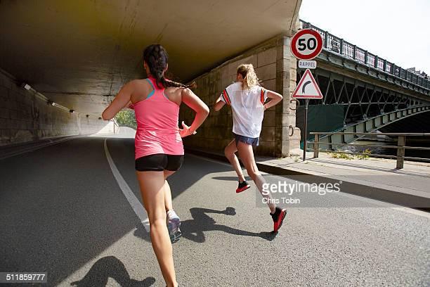Women running through tunnel