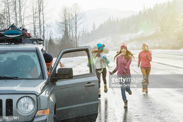 Women running to car in winter