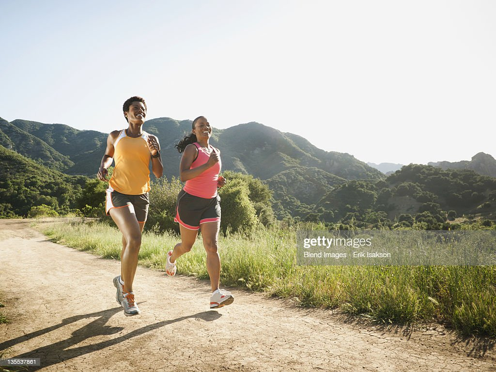 Women running together on remote trail : Stock Photo
