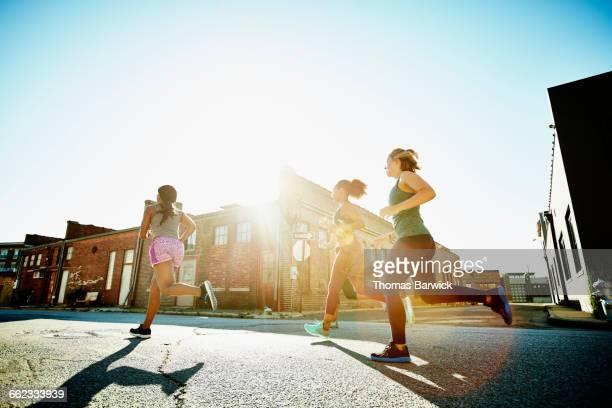 Women running together on urban street at sunrise