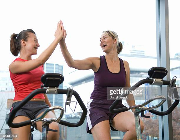Women s on exercise bikes, giving each other high-five in gym, smiling