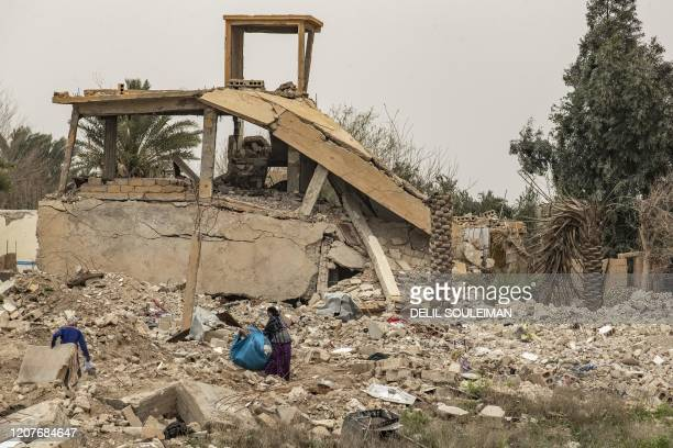 Women salvage items from the rubble of a destroyed house in the eastern Syrian village of Baghouz on March 13 a year after the fall of the Islamic...