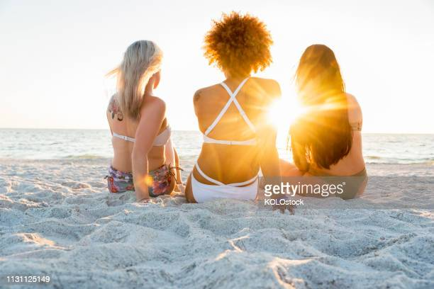 women sat at the beach watching the sunset - female friendship stock pictures, royalty-free photos & images
