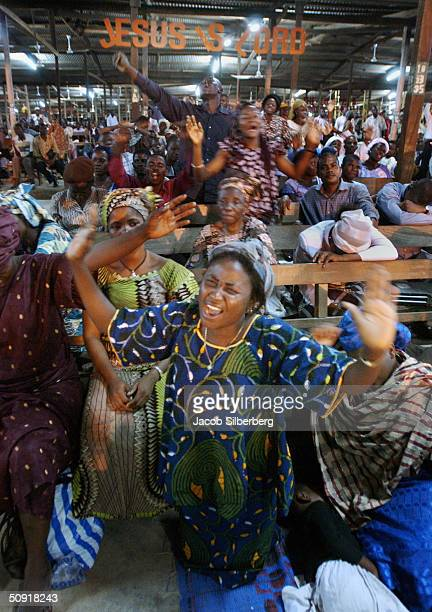 Women scream their praise to God while kneeling as others sleep on and between pews at an all night Pentecostal mass held by the Redeemed Church of...