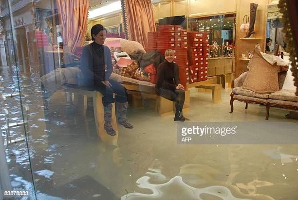 Women seat on a table while water rises in their shoe shop during floods on December 1 2008 in Venice Authorities in the Italian city of Venice...