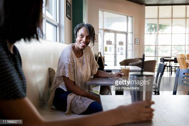 women seated at separate tables speak with each other - stranger stock pictures, royalty-free photos & images