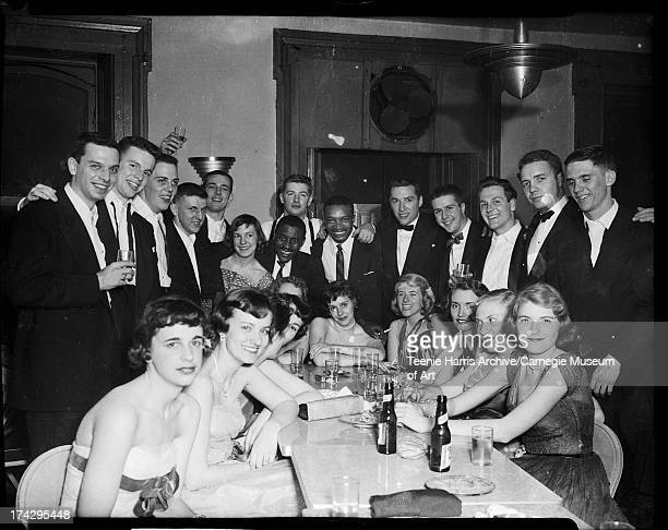 Women seated at table with drinks surrounded by Delta Tau Delta Fraternity members drummer Harold 'Brushes' Lee and Walt Harper in center for...