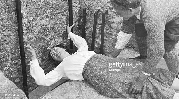 A women seen here with the aid of her gentleman friend kissing the Blarney stone at Blarney Castle 22 August 1935