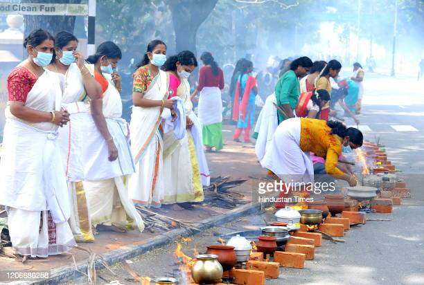 Women seen wearing facemasks amid rising Coronavirus scare, as they offer Pongala -- a gruel made of rice, jaggery, ghee and coconut during Attukal...