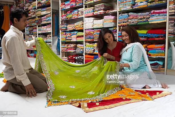 women selecting sari in sari shop - sari stock pictures, royalty-free photos & images