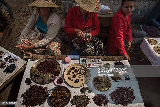 Women sell rough and cut stones on a Mogok downtown street market