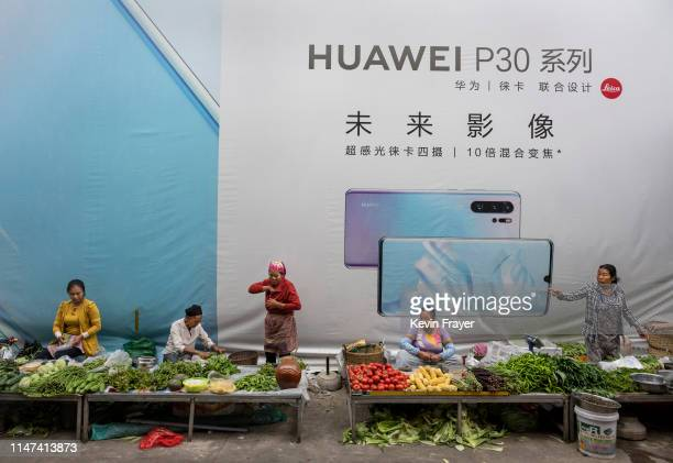 Women sell vegetables in front of a billboard advertising smartphones for China's Huawei Technologies Co on June 1 2019 in Mangshi Yunnan Province...