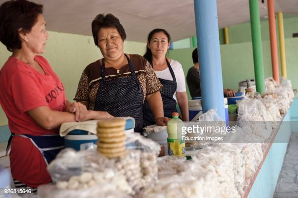 Women selling kumis and dry salty kurt cheese balls at road side stand near Altyn Emel Park Kazakhstan