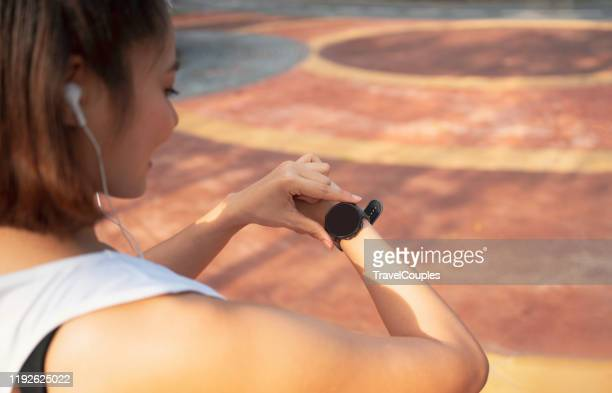 women setting up the fitness smart watch for running. young fitness women runner checking time from smart watch. young woman checking heart rate while jogging in the park. - active lifestyle stock pictures, royalty-free photos & images