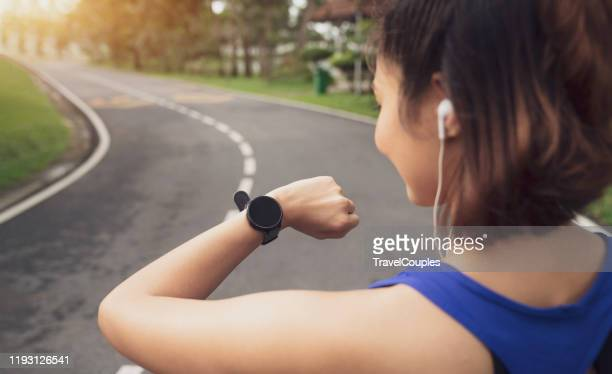 women setting up the fitness smart watch for running. young fitness women runner checking time from smart watch. young woman checking heart rate while jogging in the park. - checking sports stock pictures, royalty-free photos & images
