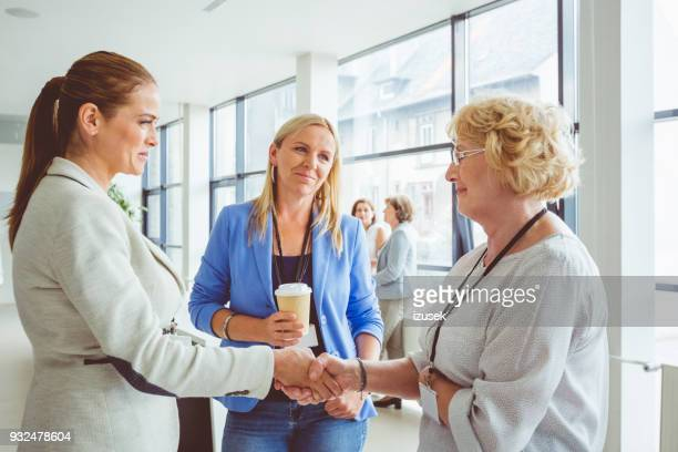 women shaking hands during conference - izusek stock pictures, royalty-free photos & images