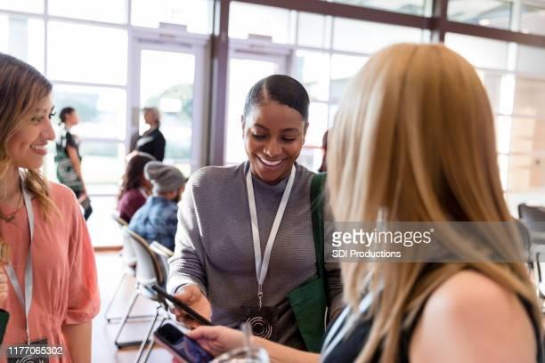 women share smart phone images at conference break time - riunione municipale foto e immagini stock