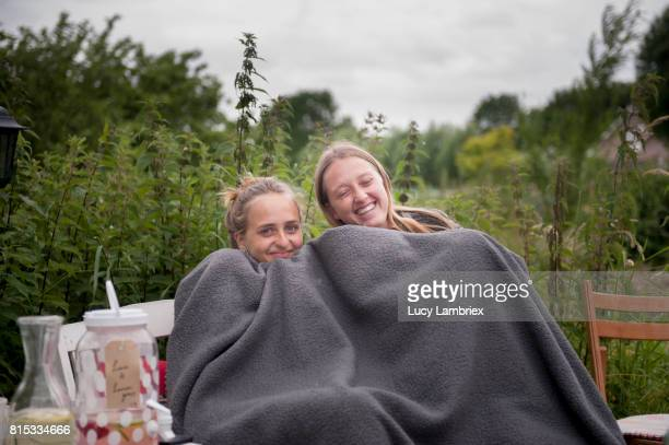 Women sharing a blanket outdoors
