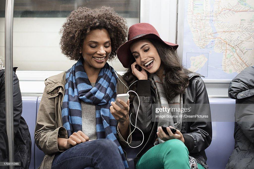 Women sharing earphones on subway : Stock-Foto