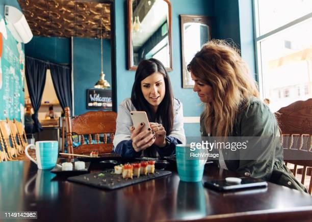 les femmes partageant les options d'investissement au déjeuner - expliquer photos et images de collection