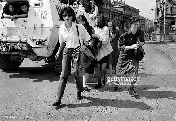 Women shelter behind a UN armoured personnel carrier as they cross 'Sniper Alley' during the siege of Sarajevo in 1995.
