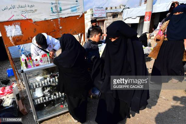 Women shop on March 28 2019 from a stall in the souk or market of AlHol camp for displaced people in northeastern Syria which currently brims with...