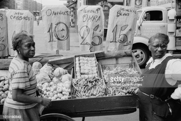 Women shopping at a market in Harlem New York City June 1957