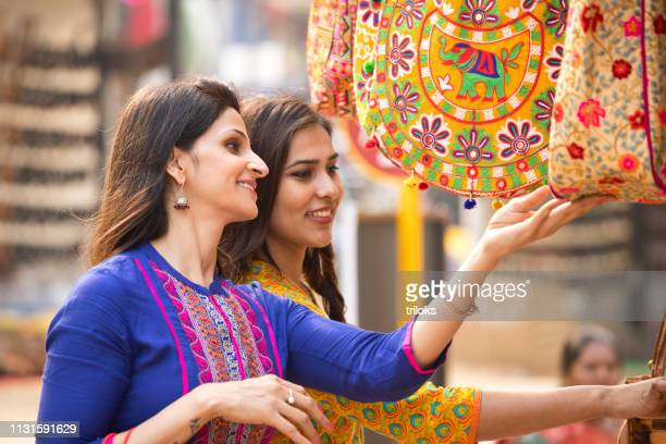 women shopping for bag at market - india market stock photos and pictures