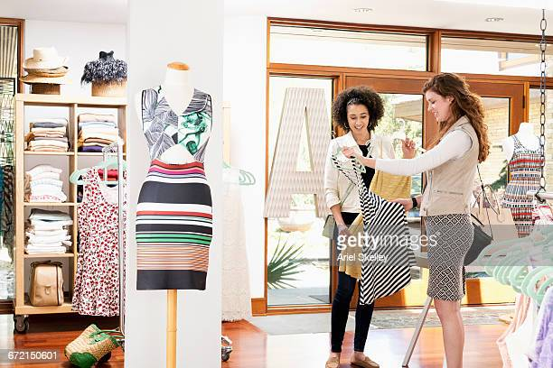 Women shopping in clothing store examining dresses