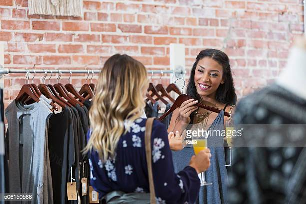 Women shopping in clothing store having drinks