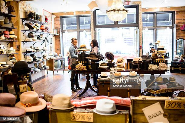 women shopping in hat store - commercial event stock photos and pictures