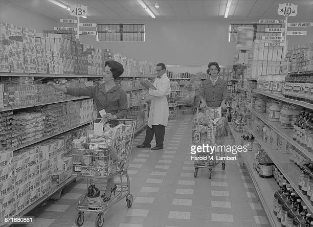 women shopping in supermarket with shop assistants standing behind - escrita ocidental - fotografias e filmes do acervo