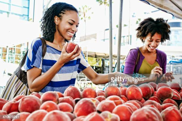 Women shopping together at fruit stand
