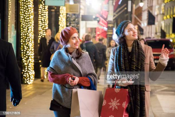 women shopping, walking in decorated street. - cold temperature stock pictures, royalty-free photos & images