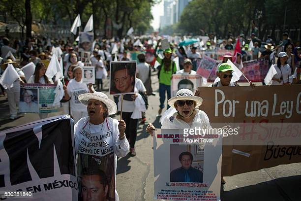 Women shout slogans and hold photographs of their disappeared sons during a march on Mother's Day on May 08 2016 in Mexico City Mexico Mothers and...