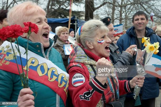 TOPSHOT Women shout slogans as they take part in a rally marking the third anniversary of Crimea voting to leave Ukraine and join the Russian state...