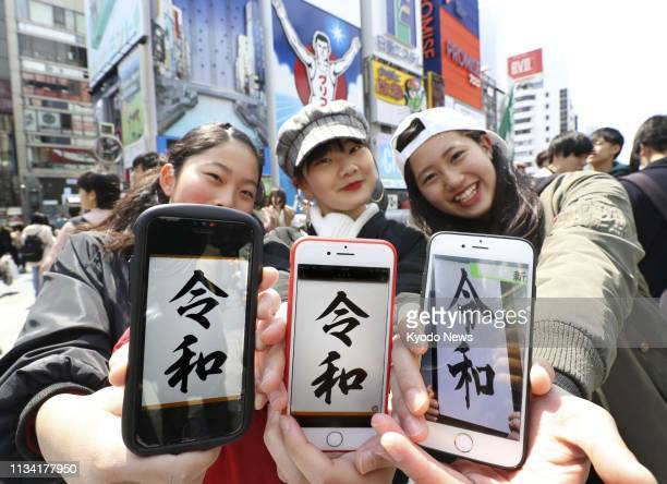 Women show smartphone screens showing the name of Japan's new era Reiwa in Osaka western Japan on April 1 following its announcement by the...