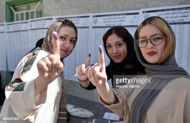 Women show their inkstained fingers after casting their ballots during Iran's 12th presidential election at Irshad Mosque in ShahreRay county of...