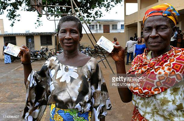 Women show their voting cards in Lome on July 25 2013 during Togo's parliamentary elections delayed by months of protests with the opposition seeking...
