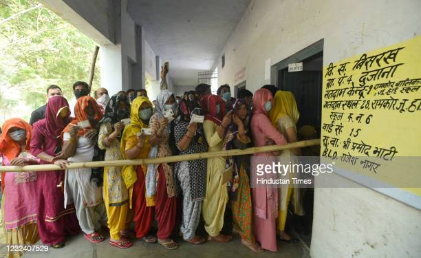 Women show voter ID cards before casting their votes in the second phase of Panchayat elections at Dujana village on April 19, 2021 in Noida, India.