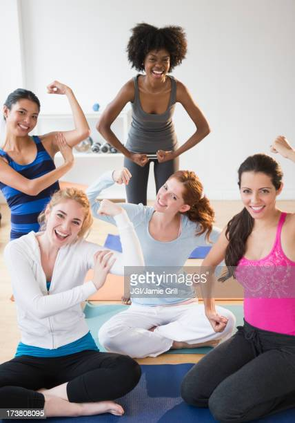 Women showing muscles on yoga mats