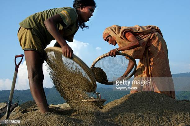 Women sifting sand on the banks of the Mari river in Jaflong Bangladesh The river coming from the Himalayas of India brings millions of tons of stone...