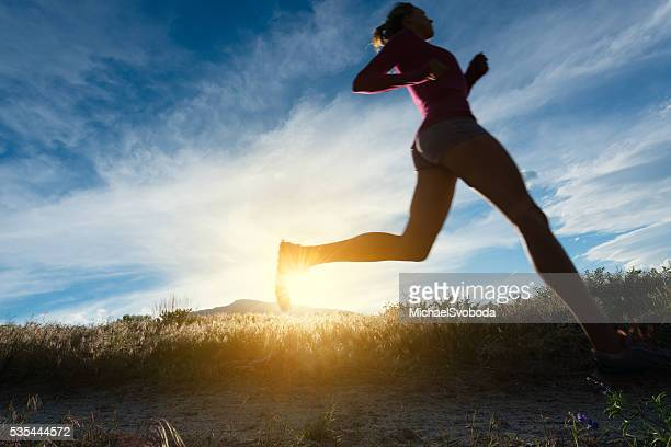 Women Silhouette Trail Runner Running At Sunset In The Mountains