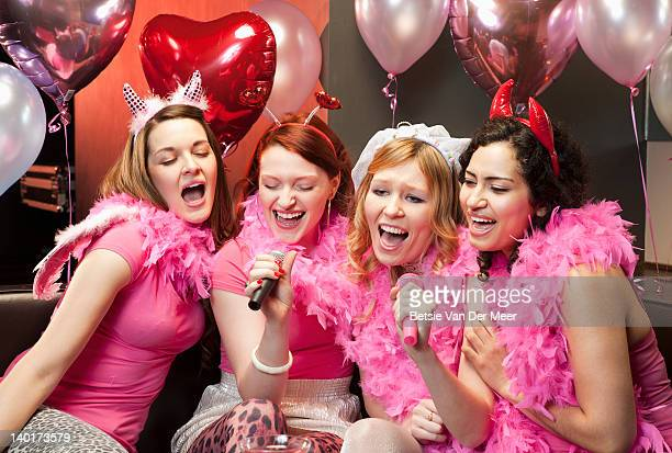 women singing karaoke at hen night party. - only young women stock pictures, royalty-free photos & images